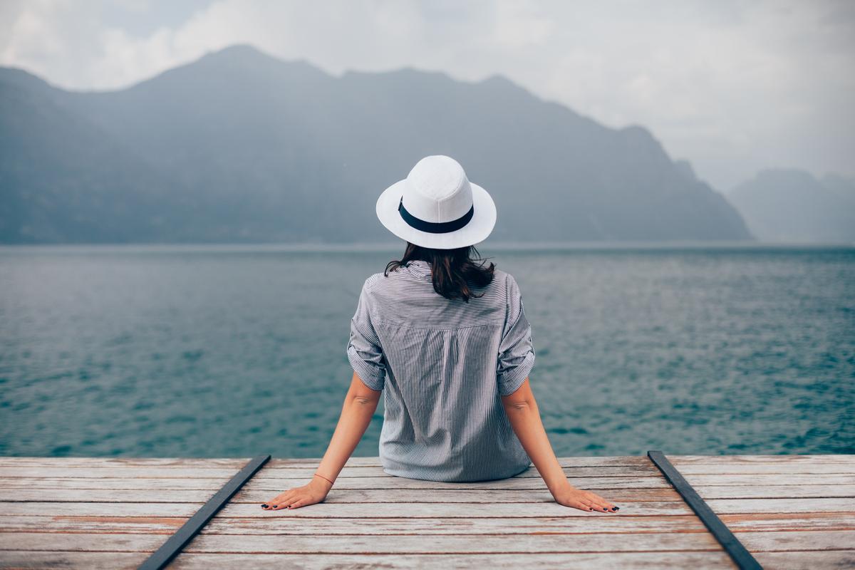 海を眺める帽子を被った女性